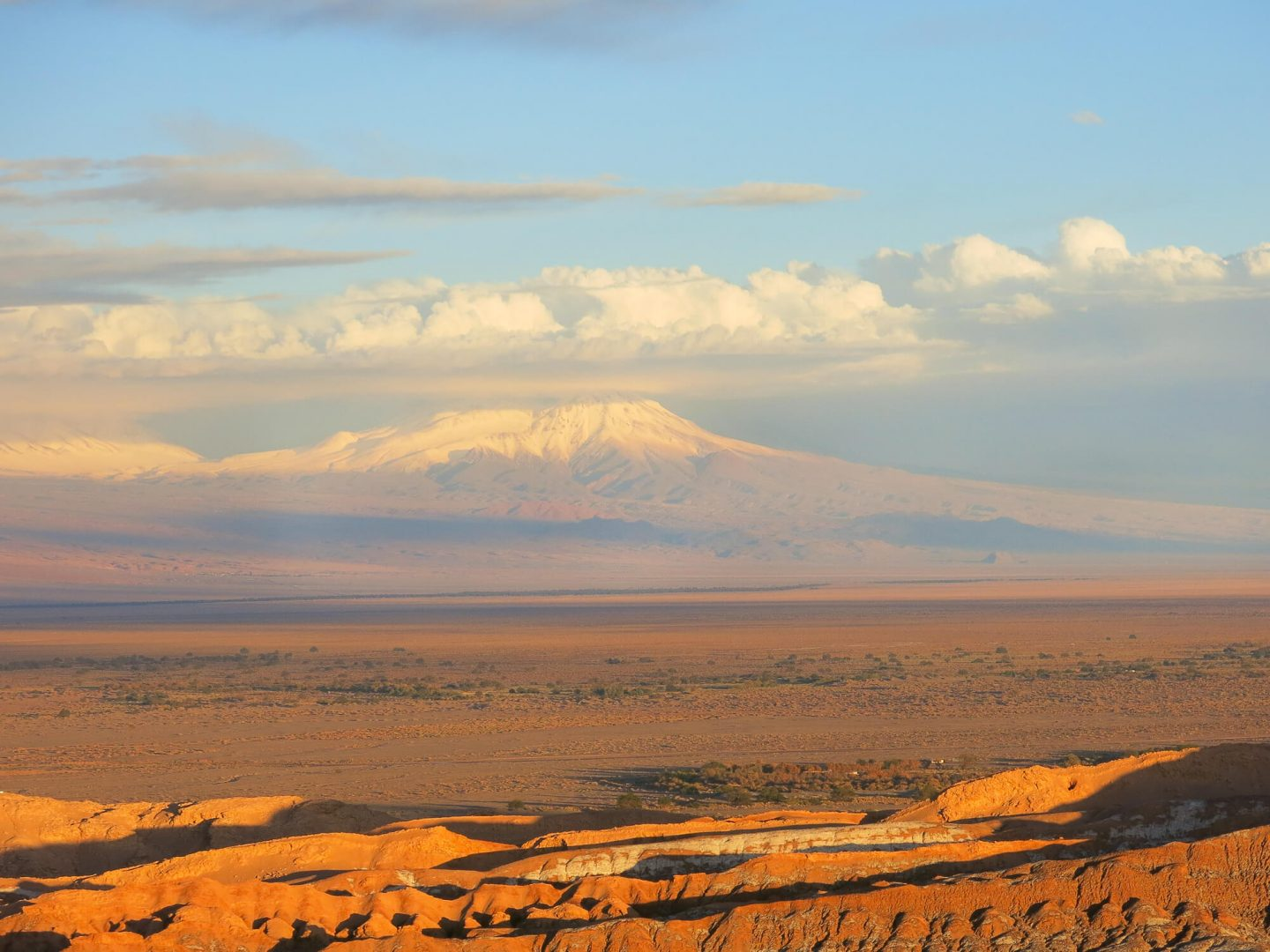 The sun setting over El Valle de la Luna – The Moon Valley in the Atacama Desert, Chile. With volcanoes in the background. Full round up of the different tours in the Atacama Desert.   Dalton-Banks