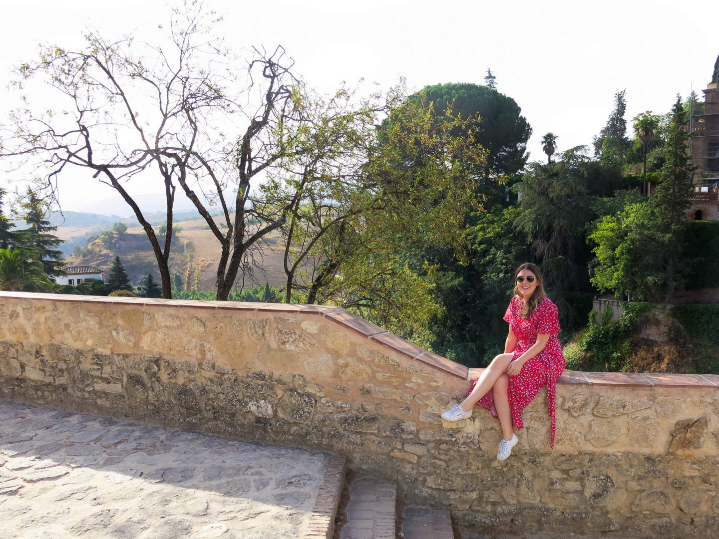 Girl sitting on a wall in Ronda. Ronda is a great day trip from Marbella, which is near the luxury 5 star hotel Kempinski Bahía, Spain