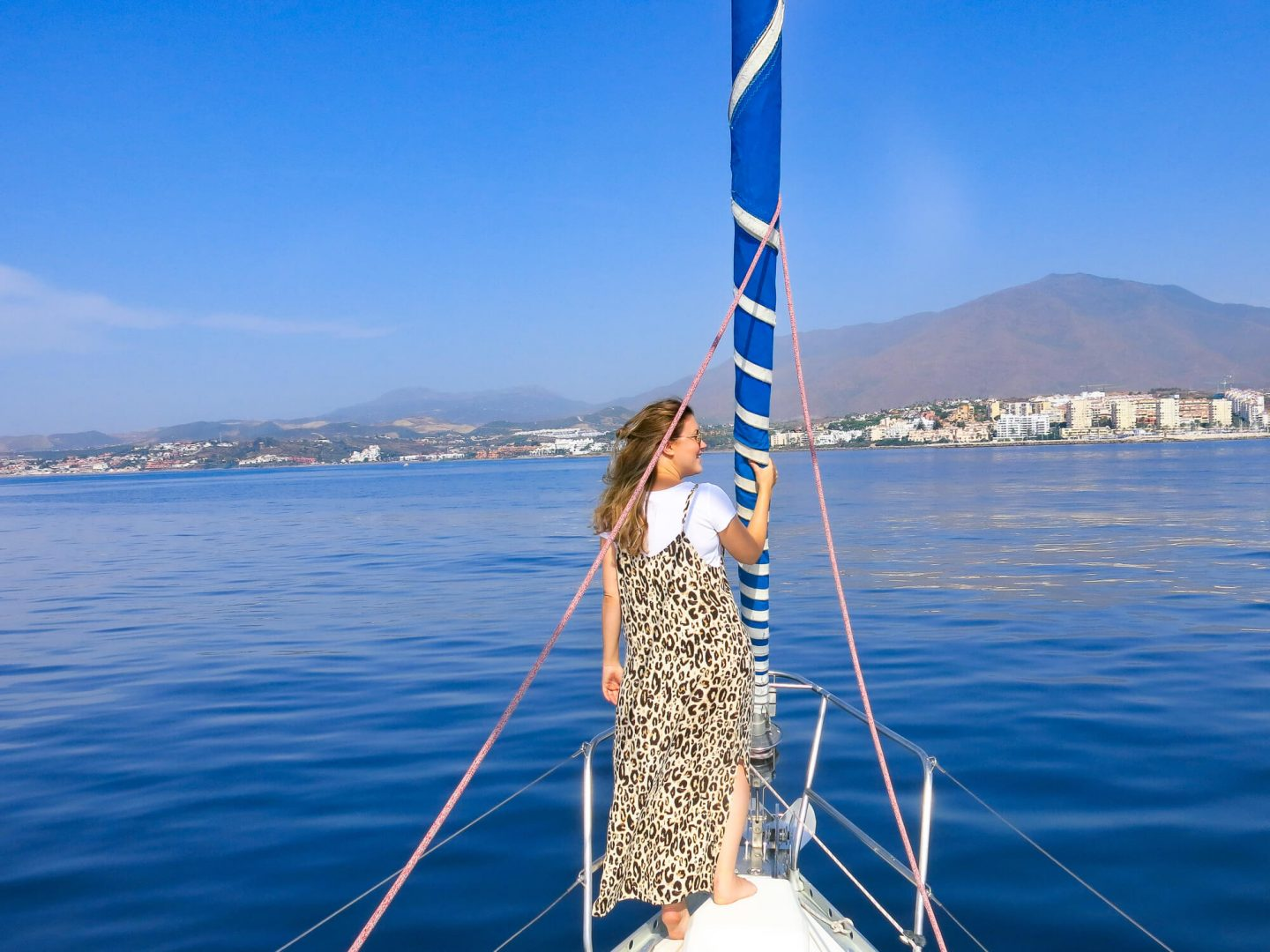 Woman on a boat, trying to spot dolphins off the shore of Andalusia. One of the day trips offered by Kempinski Hotel Bahía, Spain